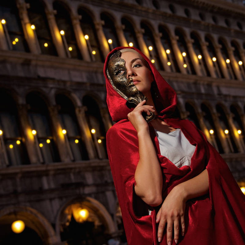 Lady in a mask wearing a red cape