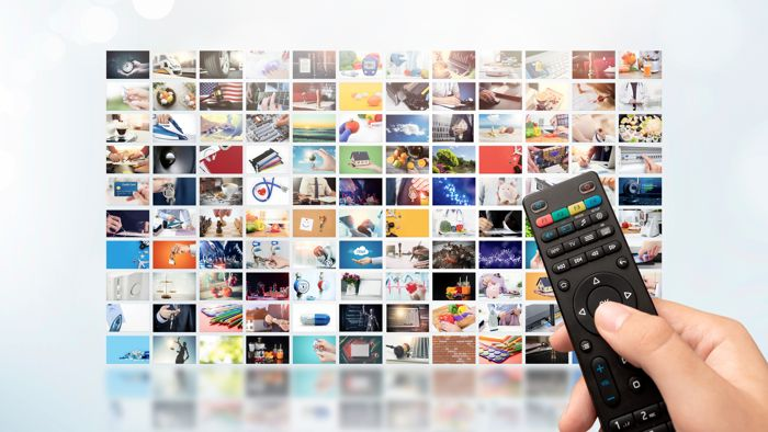 person holding remote control choosing tv shows